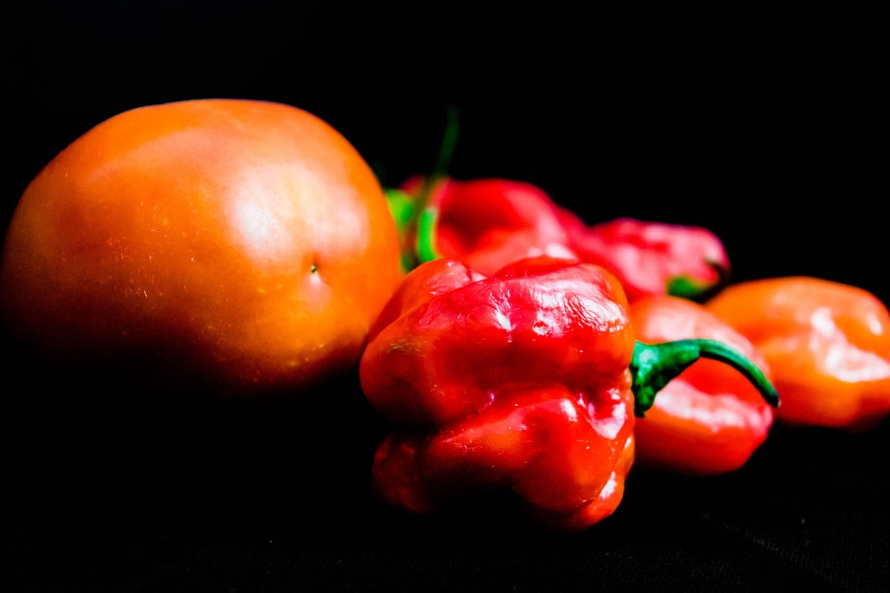 Beautiful fresh red tomato and scotch bonnet peppers isolated on black background. Red Atarodo or Ose ototo isolated on black background