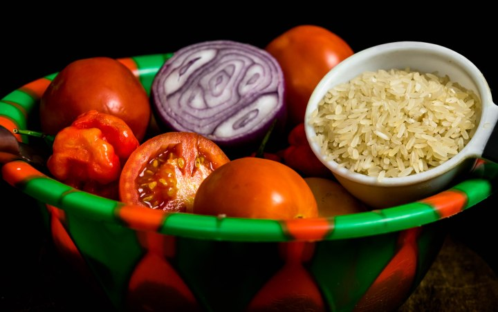 Rice, Sliced tomato and sliced onion, Scottish bonnet peppers in green and red plastic bowl for Nigerian stew concept isolated on black background